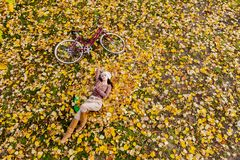 Young woman in autumn forest. Young woman with bicycle in the autumn leaves stock photo