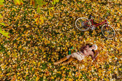 Young woman in autumn forest. Young woman with bicycle in the autumn leaves royalty free stock photography