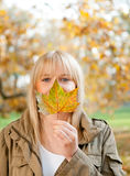 Young woman with autumn leaf. Beautiful young blond woman with autumn leaf stock image