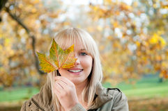 Young woman with autumn leaf. Beautiful young blond woman with autumn leaf royalty free stock images