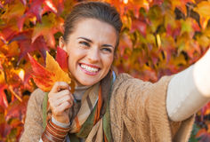 Young woman with autumn leaf making selfie Stock Photo