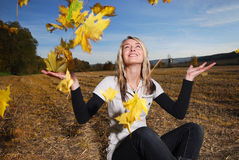 Young woman with autumn leafs Royalty Free Stock Photos
