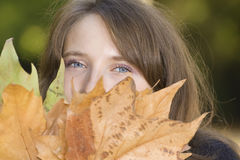 Young woman with autumn leaves. Portrait of young woman with autumn leaves stock photography