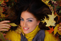 Young woman with autumn leaves. Laying down stock image