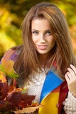 Young woman with autumn leaves. In hand and fall yellow maple garden background stock photography