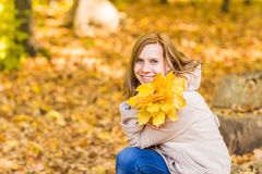 Young woman with autumn leaves in hand and fall yellow maple garden background Stock Photo