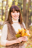 Young woman with autumn leaves in hand and fall yellow maple garden background Royalty Free Stock Photo