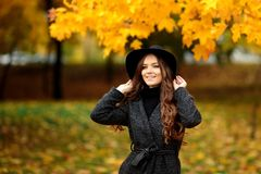 Woman with autumn leaves in hand and fall yellow maple garden background Royalty Free Stock Photo