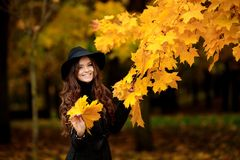 Woman with autumn leaves in hand and fall yellow maple garden background. Young woman with autumn leaves in hand and fall yellow maple garden background Royalty Free Stock Images