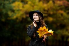 Woman with autumn leaves in hand and fall yellow maple garden background. Young woman with autumn leaves in hand and fall yellow maple garden background Royalty Free Stock Photos