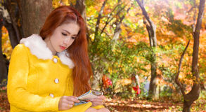 Young woman with autumn leaves in maple garden. Stock Images