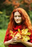 Young woman with autumn leaves in park Stock Photos