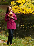 Young woman with autumn leaves in park Royalty Free Stock Photos