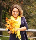 Young woman with autumn leaves in park Royalty Free Stock Image