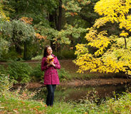 Young woman with autumn leaves in park Stock Photography