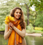 Young woman with autumn leaves in park Royalty Free Stock Images