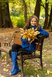 Young woman with autumn leaves sitting on bench. Young elegant woman with autumn leaves sitting on bench royalty free stock photo