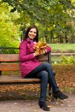 Young woman with autumn leaves sitting on bench. Young elegant woman with autumn leaves sitting on bench royalty free stock images