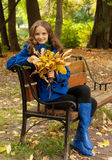 Young woman with autumn leaves sitting on bench. Young elegant woman with autumn leaves sitting on bench stock photo