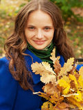 Young  woman with autumn leaves sitting on bench Stock Images