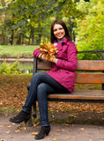 Young woman with autumn leaves sitting on bench Stock Photo