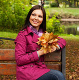 Young  woman with autumn leaves sitting on bench Stock Image