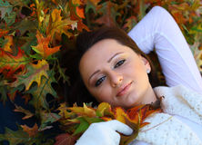Young woman with autumn leaves smiling. With pale skin royalty free stock photos