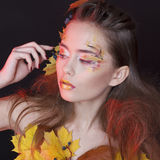 Young woman with autumn make up and leaves on head and her body. Young beautiful woman with autumn make up and leaves on head and body royalty free stock image