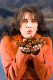 Young woman with autumn mood. Young woman blowing leaves from your hand royalty free stock photo