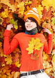 Young woman in autumn orange leaves. Outdoor stock photography