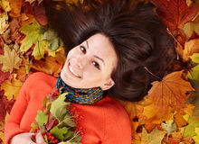 Young woman in autumn orange leaves. Outdoor royalty free stock photography