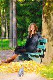 Young woman in autumn park. Young woman is sitting on the bench in autumn park and looking at camera royalty free stock photo