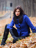 Young woman in the autumn park. Young woman sitting in the autumn park royalty free stock photography