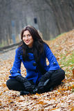 Young woman in the autumn park. Young woman sitting in the autumn park royalty free stock photos