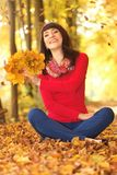 Young woman in autumn park. Young woman with autumn leaves in hand orange and yellow maple royalty free stock photo