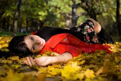 Young woman in autumn park on ground Royalty Free Stock Image