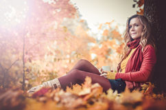 Young woman in autumn park,. Young woman sitting in beautiful autumn park stock images