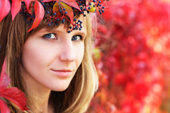Young woman autumn portrait in crown of red autumn leaves Royalty Free Stock Photography