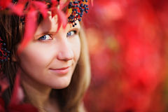 Young woman autumn portrait in crown of red autumn leaves Stock Photography
