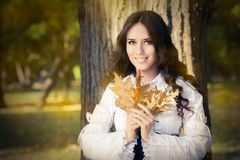 Young Woman Autumn Portrait. Pretty girl in the park, with autumn foliage stock photography
