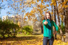 Young woman in autumn yellow park showing a thumbs Royalty Free Stock Photos