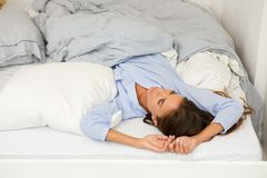 Young woman awake in bed looking up Stock Images
