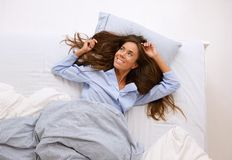 Young woman awake in bed and smiling Royalty Free Stock Image