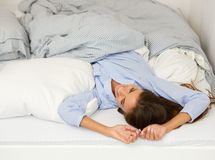 Young woman awake in bed smiling Royalty Free Stock Photography