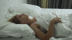 Young woman awakening in comfortable cozy bed on soft white pillow and sheets. Young woman awakening in comfortable cozy fresh bed on soft white pillow and stock video