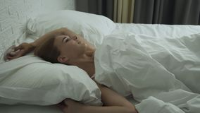 Young woman awakening in comfortable cozy fresh bed and takes smartphone. stock video footage
