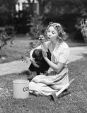 Young woman, with an ax next to her, hugs a turkey Royalty Free Stock Photo