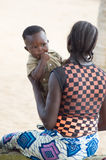 Young woman with baby. Abidjan, Cote d'Ivoire-August 29, 2015: A young woman sitting on a coconut tree trunk is playing with her baby that has his finger in his Stock Image