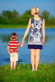 Young woman and a baby boy holding hands on lake coast Royalty Free Stock Photos