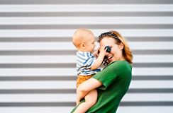 Young woman with a baby boy standing against the wall. Stock Photo